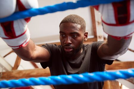 Male Boxer In Gym Wearing Boxing Gloves Leaning On Ropes Of Boxing Ring