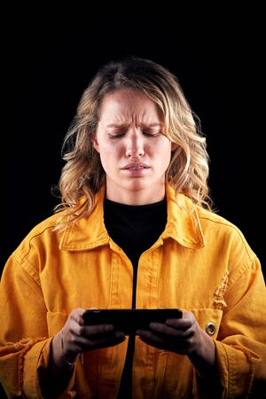 Studio Shot Of Unhappy Woman Holding Mobile Phone Being Bullied Online