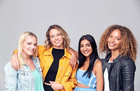 Group Studio Portrait Of Multi-Cultural Female Friends Smiling Into Camera Together