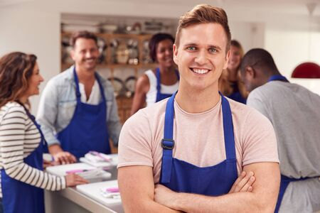 Retrato del hombre sonriente con delantal tomando parte en la clase de cocina en la cocina