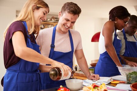 Étudiants adultes masculins et féminins ajoutant de l'huile d'olive au plat dans la classe de cuisine de cuisine