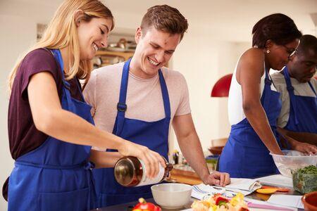 Mannelijke en vrouwelijke volwassen studenten die olijfolie toevoegen aan een gerecht in de kookcursus in de keuken