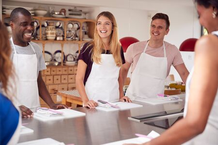 Male And Female Students Standing With Chopping Boards At Start Of Cookery Class In Kitchen