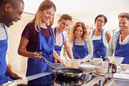 Enseignante faisant des crêpes sur une cuisinière en cours de cuisine en tant qu'étudiants adultes regardent sur