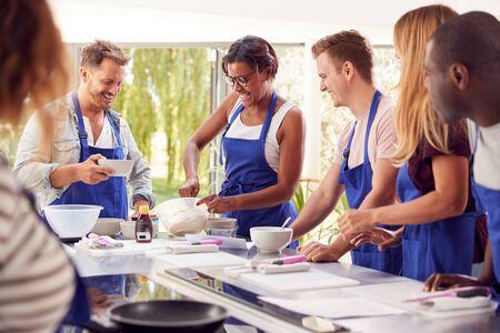 Étudiants en cours de cuisine Mélanger les ingrédients pour la recette dans la cuisine