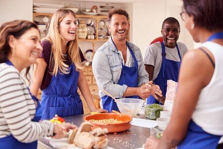 Männliche und weibliche erwachsene Studenten, die Zutaten für das Gericht im Küchenkochkurs vorbereiten?