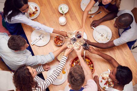 Coup de frais généraux d'hommes et de femmes faisant des toasts en train de manger un repas qu'ils ont préparé en cours de cuisine cuisine