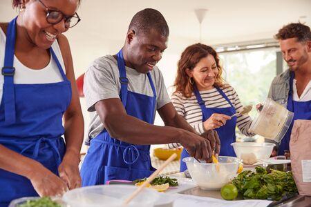 Étudiants adultes masculins et féminins préparant des ingrédients pour le plat dans la classe de cuisine de cuisine Banque d'images