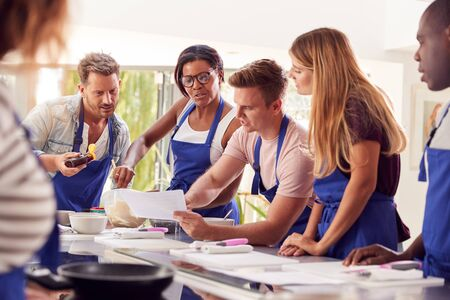 Male And Female Adult Students Looking At Recipe In Cookery Class In Kitchen