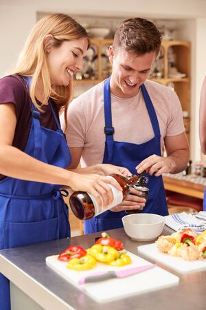 Male And Female Adult Students Adding Olive Oil To Dish In Kitchen Cookery Class Reklamní fotografie