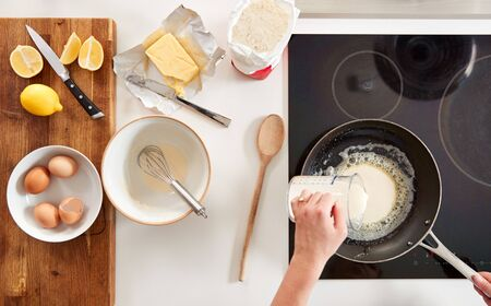 Overhead Shot Of Woman In Kitchen Pouring Batter Into Pan For Pancakes Or Crepes For Pancake Day