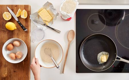 Overhead Shot Of Woman In Kitchen Mixing Ingredients For Pancakes Or Crepes For Pancake Day