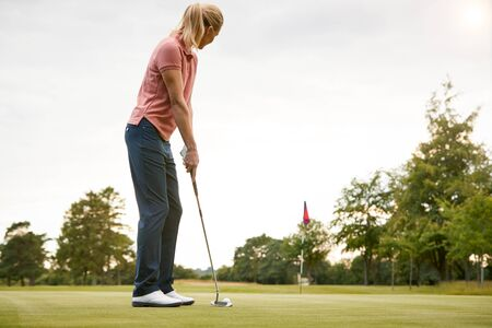 Rear View Of Female Golfer Putting Ball On Green Standard-Bild