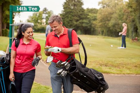 Mature Couple Playing Round Of Golf Carrying Golf Bags And Marking Scorecard