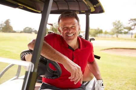 Portrait Of Mature Man Playing Golf Driving Buggy Along Course To Green On Red Letter Day