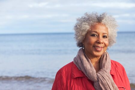 Head And Shoulders Portrait Of Active Senior Woman Walking Along Winter Beach With Sea Behind