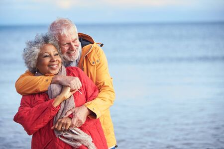 Loving Senior Couple Hugging As They Walk Along Shoreline On Winter Beach Vacation