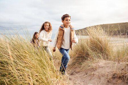 Drie kinderen die plezier hebben in het verkennen van zandduinen tijdens een winterstrandvakantie Stockfoto