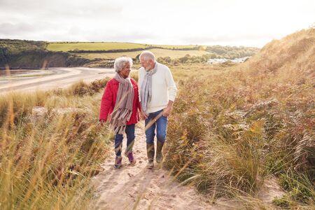 Loving Active Senior Couple Walking Arm In Arm Through Sand Dunes On Winter Beach Vacation 스톡 콘텐츠