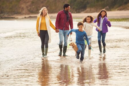 Multi-Cultural Family With Pet Dog Walking Along Beach Shoreline On Winter Vacation