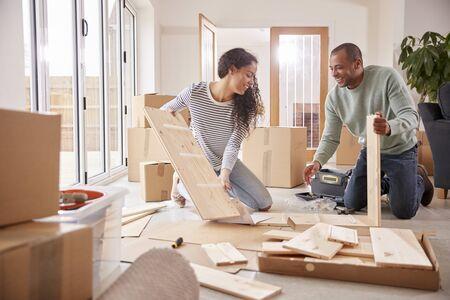 Couple dans une nouvelle maison le jour du déménagement pour assembler des meubles à assembler soi-même