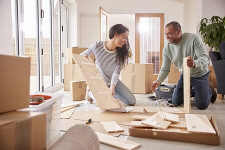 Paar in neuem Zuhause am Umzugstag zusammenbauen Selbstmontage-Möbel
