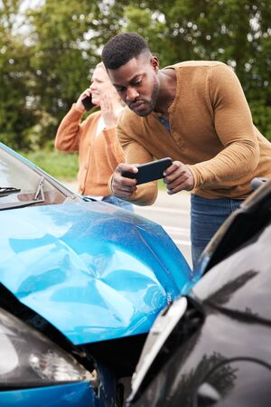 Male Motorist Involved In Car Accident Taking Picture Of Damage For Insurance Claim Stock Photo