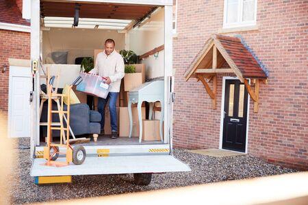 Homme déchargeant des meubles du camion de déménagement à l'extérieur de la nouvelle maison le jour du déménagement Banque d'images