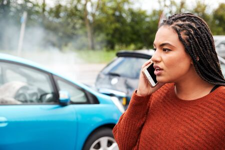 Female Motorist Involved In Car Accident Calling Insurance Company Or Recovery Service Banque d'images