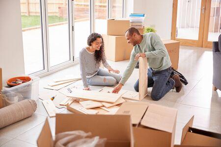 Coppia in una nuova casa il giorno del trasloco mettendo insieme mobili da assemblare