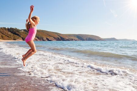 Girl Wearing Swimming Costume Having Fun Jumping Over Waves On Beach On Summer Vacation Stock fotó - 138464654