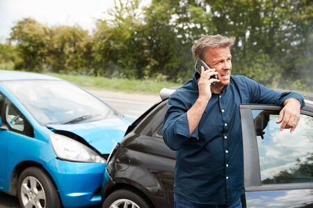 Mature Male Motorist Involved In Car Accident Calling Insurance Company Or Recovery Service Foto de archivo