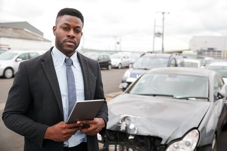 Portrait Of Insurance Loss Adjuster With Digital Tablet Inspecting Damage To Car From Motor Accident