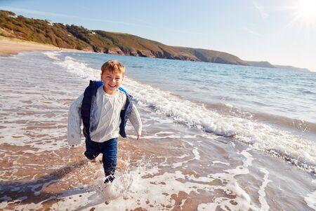 Young Boy Having Fun Running Through Waves On Beach