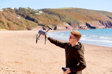 Young Man Flying Drone With Camera On Beach With Waves In Background