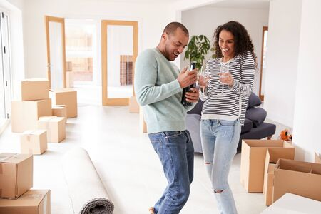 Couple Celebrating Moving Into New Home Opening Champagne