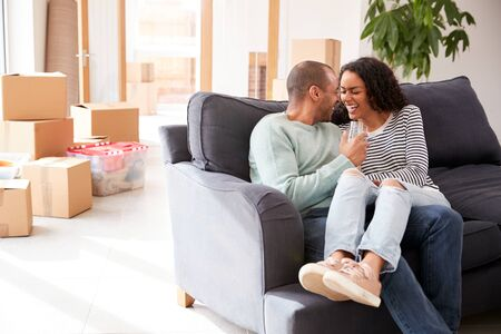 Couple Taking A Break And Sitting On Sofa Celebrating Moving Into New Home With Champagne 스톡 콘텐츠