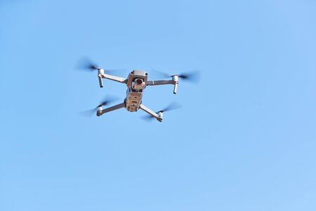 Drone With Camera Flying Against Clear Blue Sky