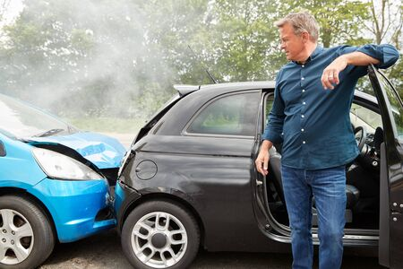 Mature Male Motorist In Crash For Crash Insurance Fraud Getting Out Of Car