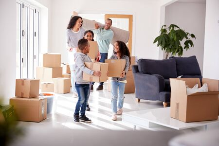Smiling Family Carrying Boxes Into New Home On Moving Day