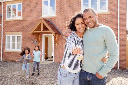 Retrato de familia sosteniendo llaves de pie fuera de casa nueva el día de la mudanza