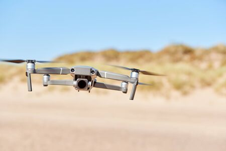 Drone With Camera Flying On Beach With Sand Dunes In Background