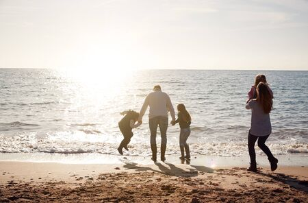 Rear View Of Family Jumping Over Waves Looking Out To Sea Silhouetted Against Sun Stock fotó
