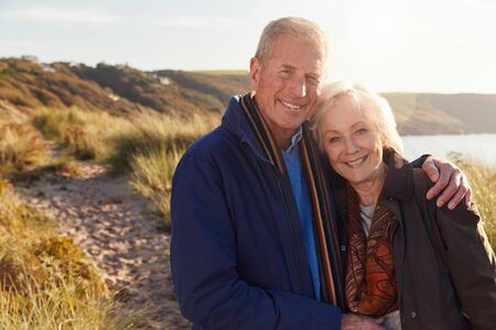Portrait Of Loving Active Senior Couple Walking Through Sand Dunes In Autumn Together