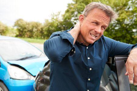 Automobiliste de sexe masculin mature avec blessure au coup du lapin dans un accident de voiture sortir du véhicule