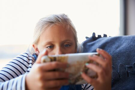 Young Girl Playing Video Games On Mobile Phone Sitting On Sofa At Home