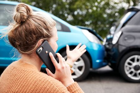 Female Motorist Involved In Car Accident Calling Insurance Company Or Recovery Service Stock Photo