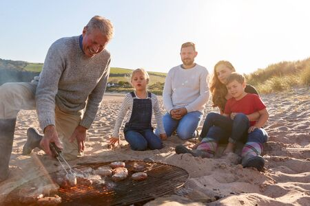 Grandfather Cooking As Multi-Generation Family Having Evening Barbecue Around Fire On Beach Vacation