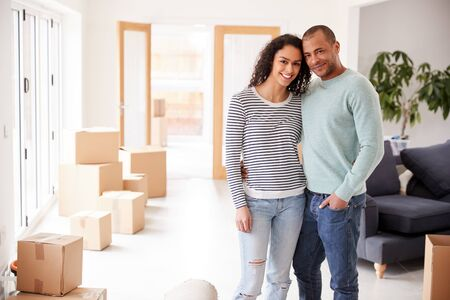 Portrait Of Loving Couple Surrounded By Boxes In New Home On Moving Day
