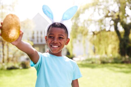 Portrait Of Boy Wearing Bunny Ears Holding Chocolate Egg On Easter Egg Hunt In Garden